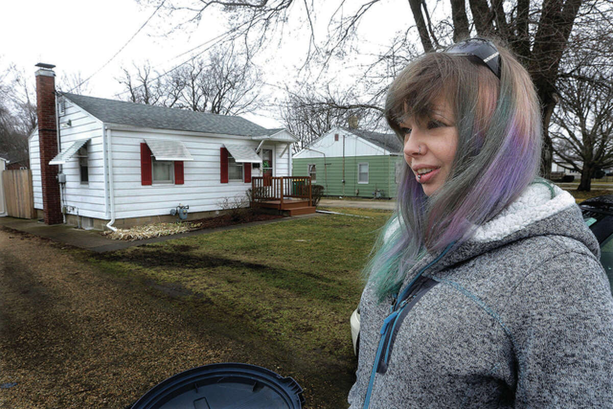 """Seth Perlman   AP Whitney Zielke, 32, stands outside her mother's house on a street where testing revealed high amounts of lead in Galesburg. Zielke said her mother """"freaked out"""" after receiving that notice but that she didn't know what to think."""