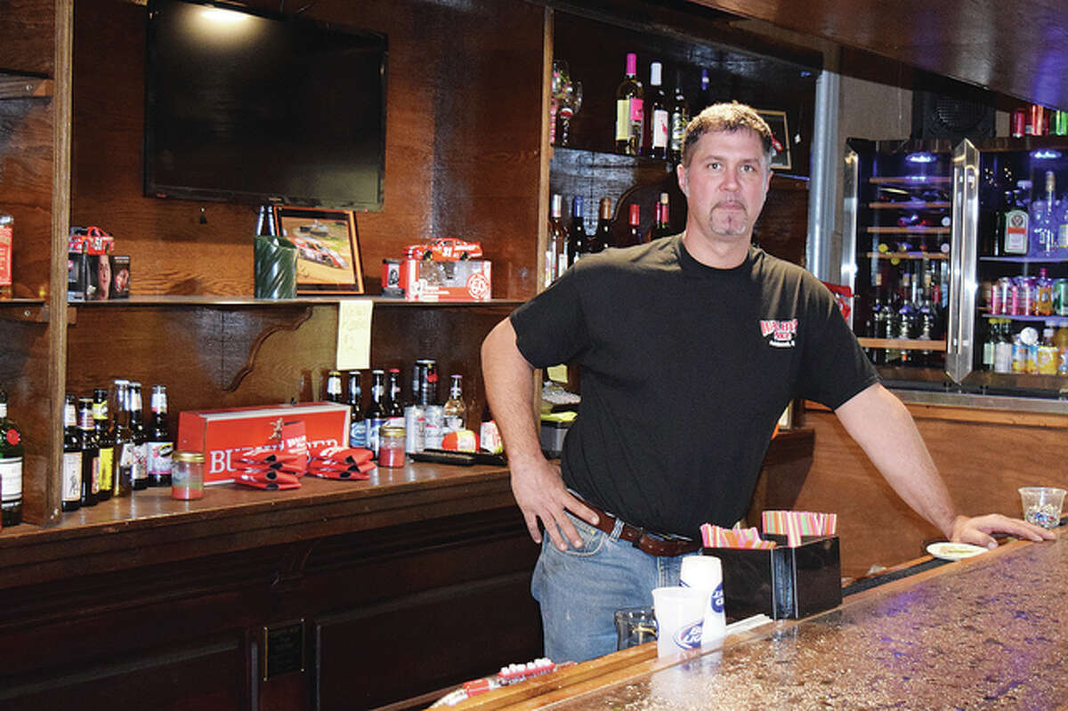 Walbys Place owner and operator Travis Wallbaum stands behind the bar in the pub area of his new business.