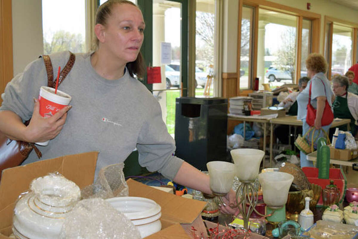 Michelle Wooldridge of Jacksonville looks through items at the Jacksonville Senior Center's flea market and bake sale Wednesday at Community Park. The sale continues today from 8 a.m. to 4 p.m. and Friday from 8 a.m. to 2 p.m.