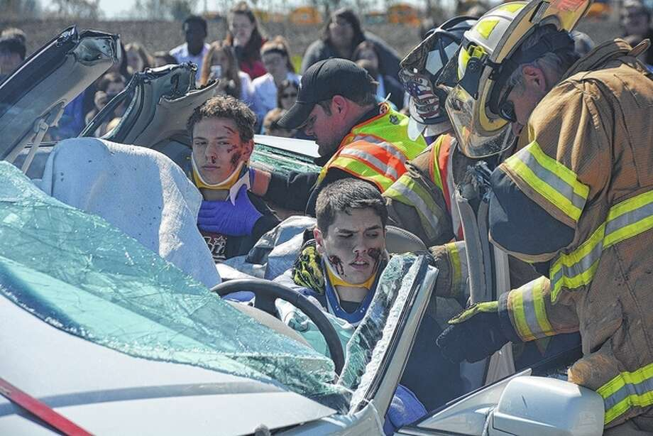 Jeff Ruzicka | Journal-Courier Pittsfield High School students Eli Ten Eyck (left) and Josh Greenwood portray victims of a traffic crash as part of an exercise Wednesday to demonstrate the dangers of such activities as drinking or texting while driving.
