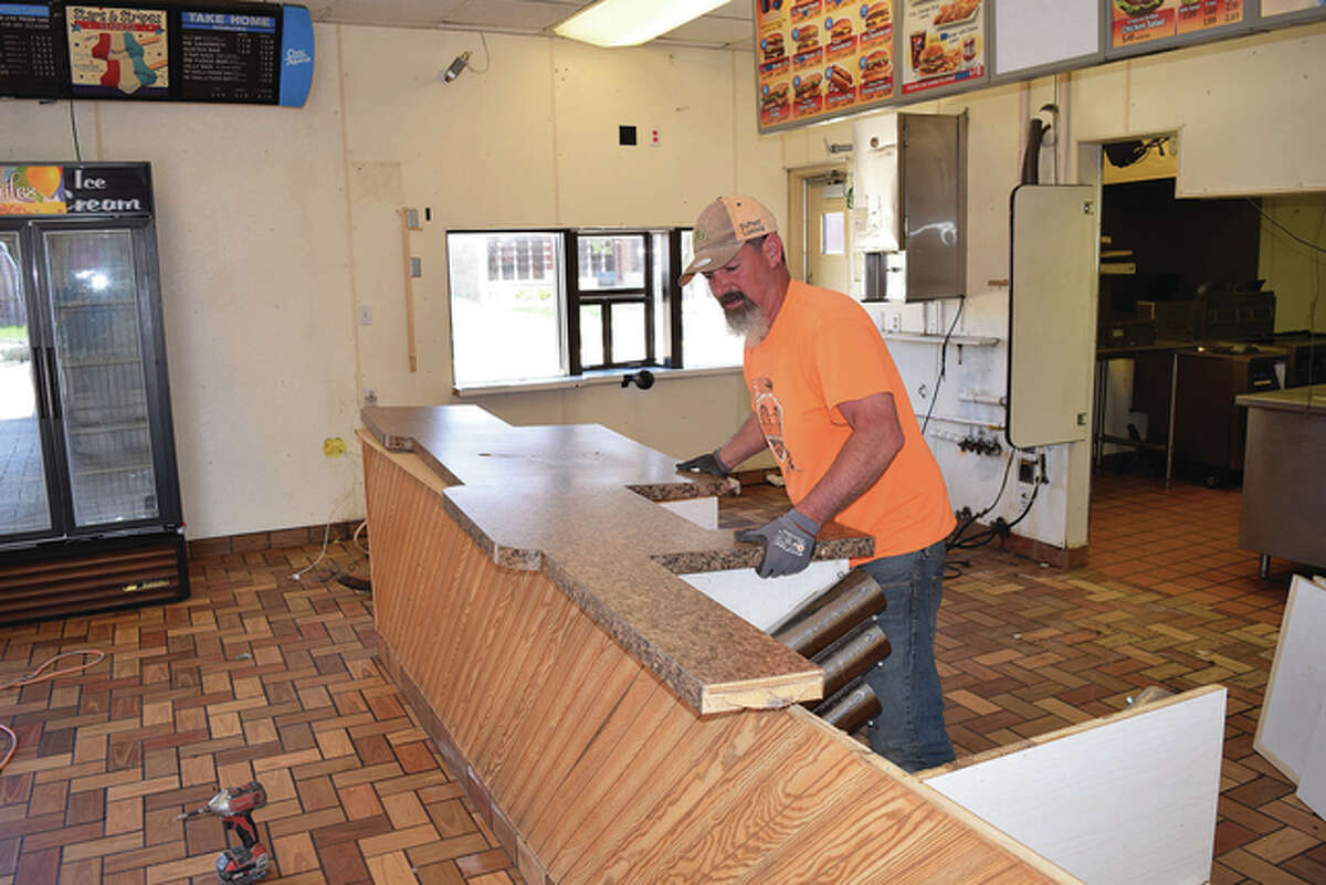 Chad Doty, a carpenter working for First Build Associates of Germantown Hills, removes the old counter Thursday at the former Dairy Queen building in Jacksonville. The building is being remodeled for a new Dairy Queen, which is expected to open in late June.