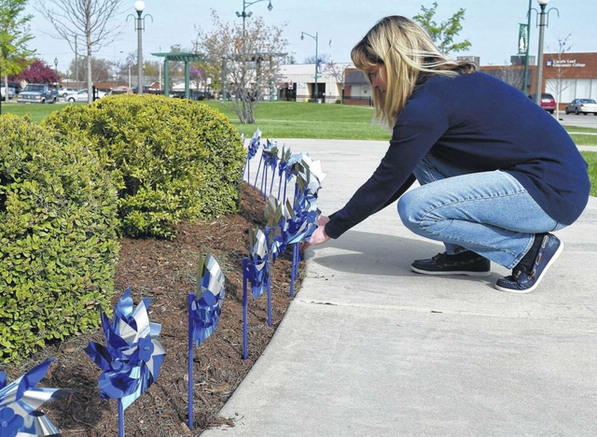 """Annette Huddleston, executive director of Hobby Horse House, straightens pinwheels in Central Park Friday. The pinwheels were placed in the park in recognition of Child Abuse Prevention Month. """"We will also be placing multicolored pinwheel bouquets in vases in downtown square businesses,"""" Huddleston said. Hobby Horse House is a child welfare agency that provides therapeutic and educational services to families in eight west-central Illinois counties."""