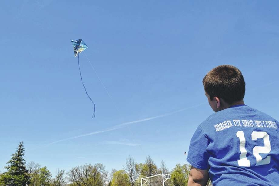 Nine-year-old Alex Doss of Jacksonville watches his kite twist in the breeze Saturday during the Let's Go Fly a Kite event in Community Park. Photo: Greg Olson | Journal-Courier