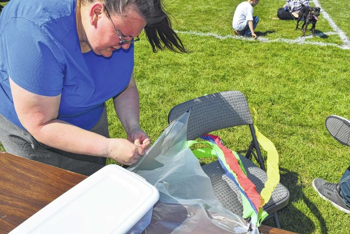 Stacey Doss of Jacksonville makes repairs to a kite Saturday at the Let's Go Fly a Kite event in Community Park.