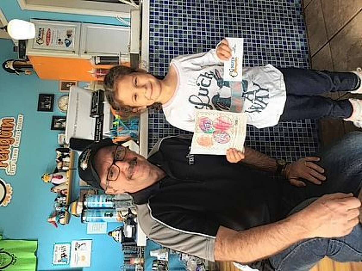 Randy Cooper, owner of the Frozen Penguin, presents Inez Stock of Chapin a gift certificate for winning the Journal-Courier's Easter coloring contest for ages 0-4.