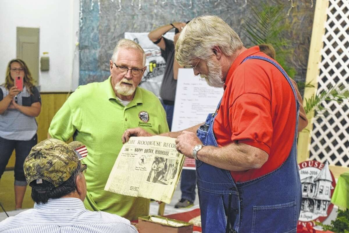 """Dick Roodhouse and Terry Hopkins look at a copy of The Roodhouse Record dated July 27, 1966, that reads """"Happy Birthday, Roodhouse."""""""