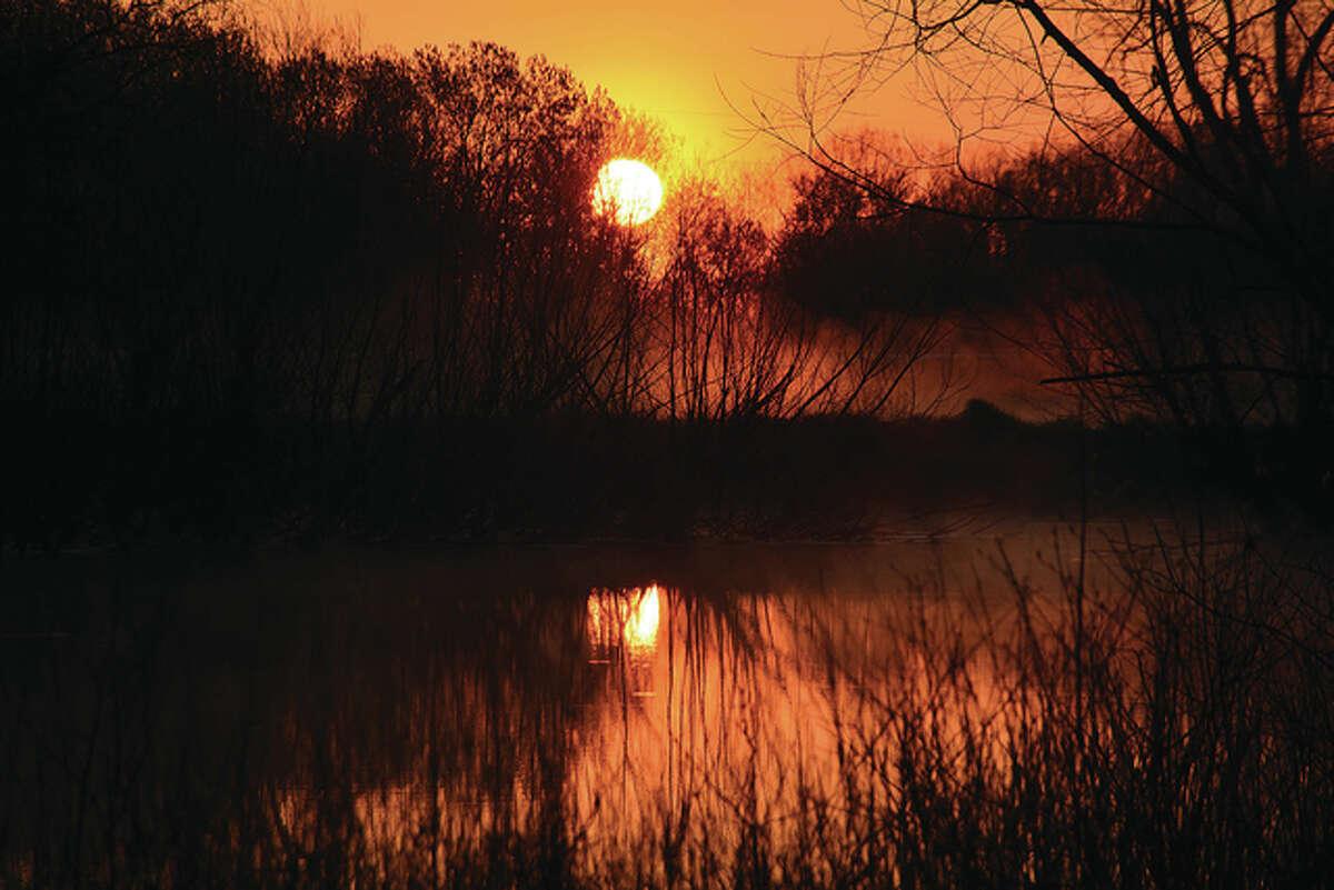 The rising sun creates an orange glow to the landscape.