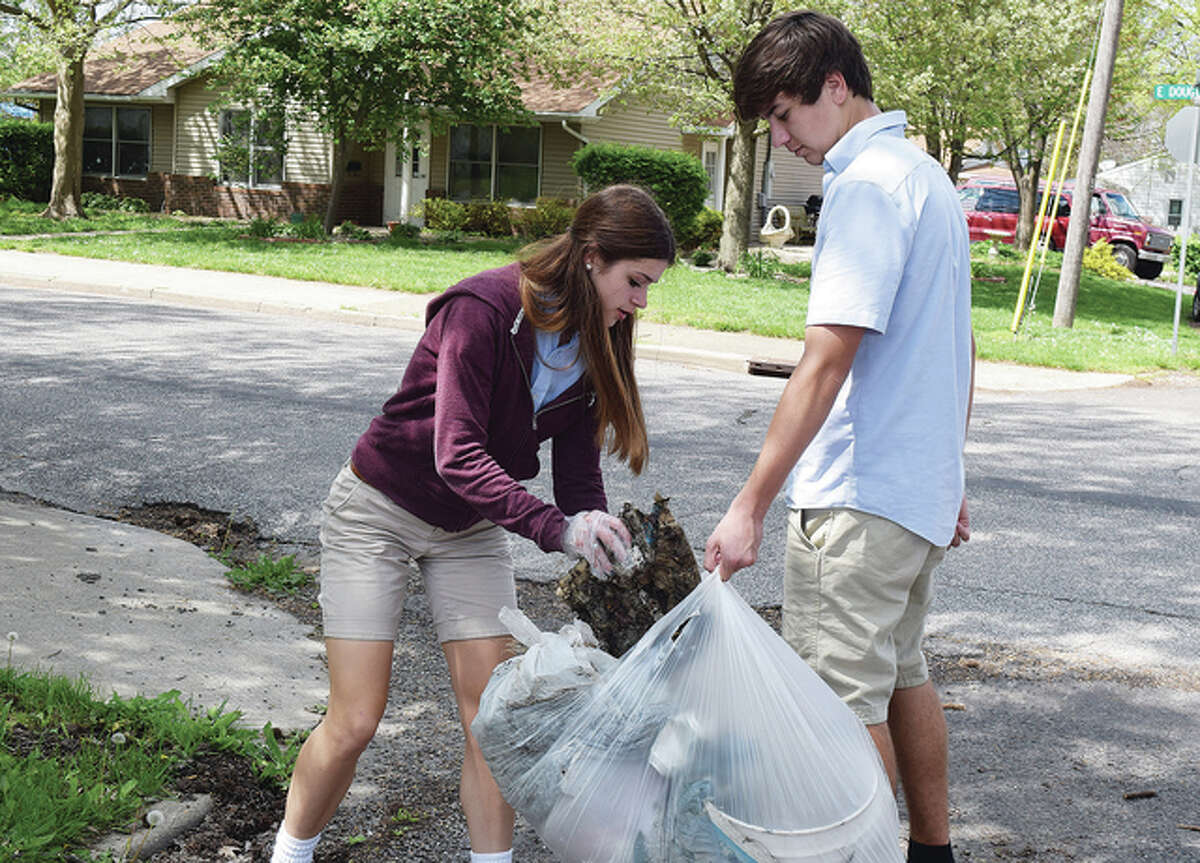 Juniors Abigail Jackson and Ethan Flinn pick up trash Friday in the neighborhood around Routt Catholic High School as a part of the school's Earth Day program.