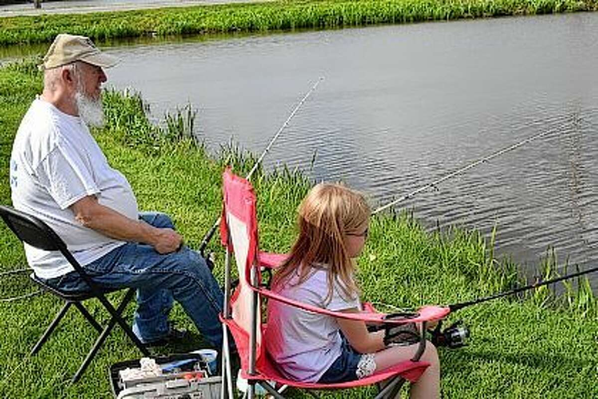 Jayci Hopper, 8, of Literberry, fishes with her grandfather, Roland Christy, of Jacksonville, Monday at Morgan Lake in Nichols Park.