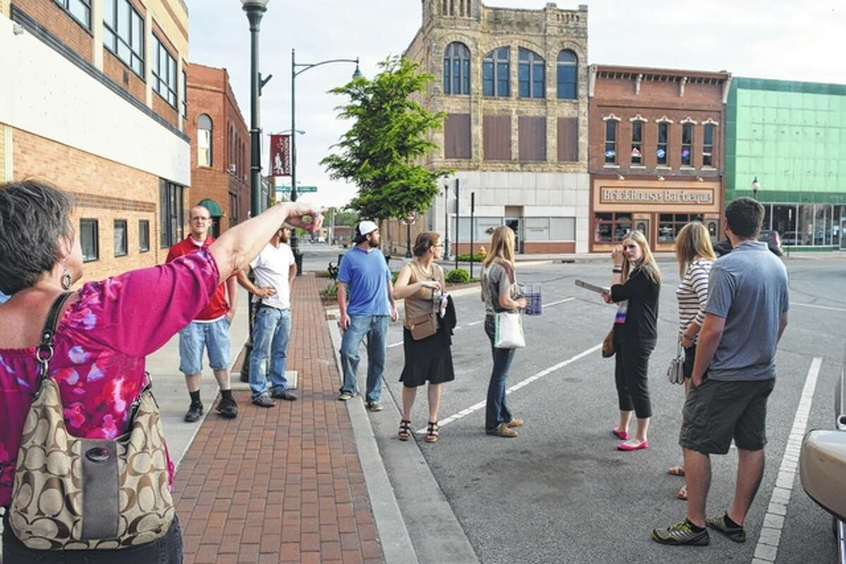 Jacksonville Main Street Executive Director Judy Tighe (left) points out some buildings on the south side of the Jacksonville square to members of the Young Professionals Network Monday evening during a walking tour of downtown.