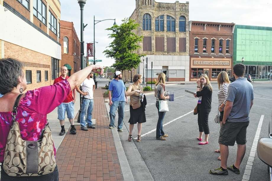 Jacksonville Main Street Executive Director Judy Tighe (left) points out some buildings on the south side of the Jacksonville square to members of the Young Professionals Network Monday evening during a walking tour of downtown. Photo: Greg Olson | Journal-Courier