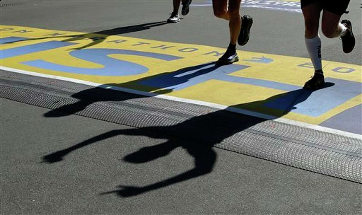 Runners cast shadows at the finish line of the 120th Boston Marathon on Monday, April 18, 2016, in Boston. AP Photo by Elise Amendola.