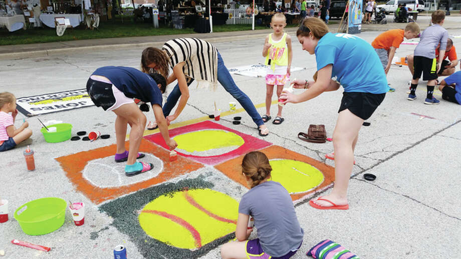 Participants in the 2015 Art in the Park event paint a square of space on the pavement around Art Zeeck Park. Photo: Submitted Photo