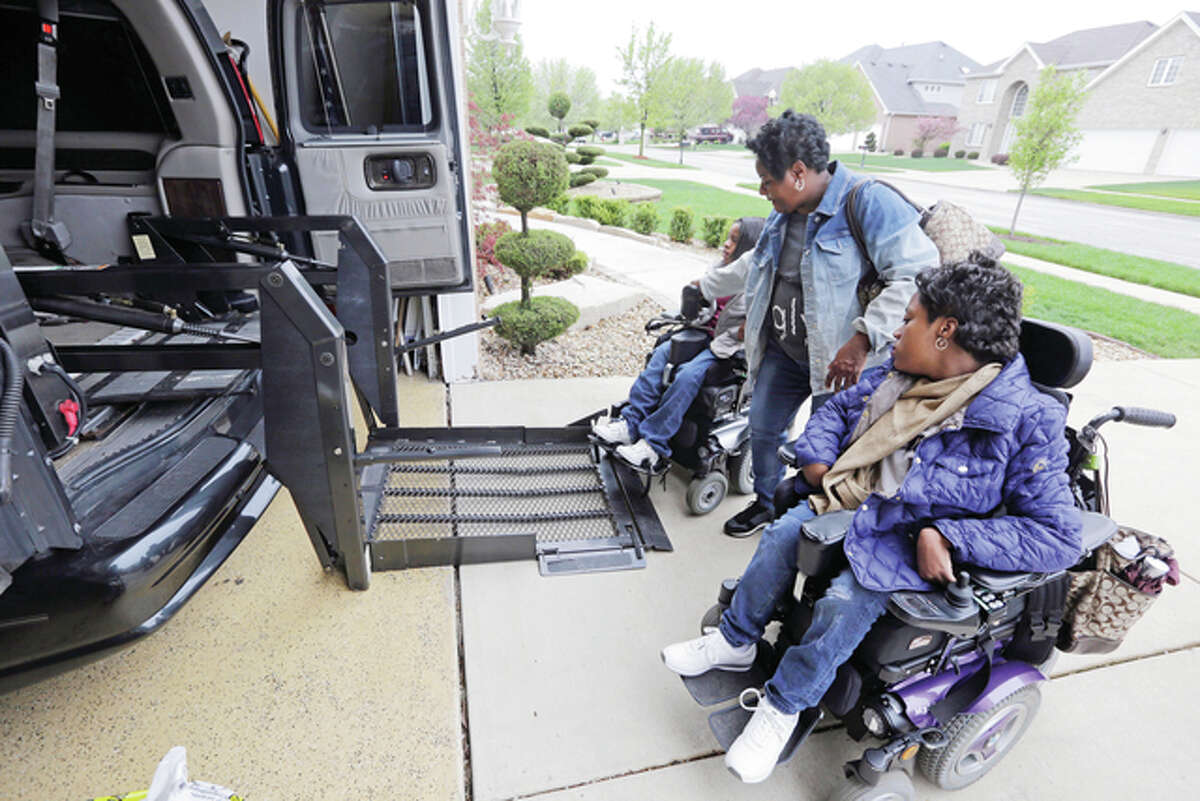 Elaine Walker helps her two daughters Dasia (left) and Melissa into the car Thursday at their home in South Holland. Illinois Gov. Bruce Rauner is cutting costs in a state budget crisis by limiting overtime worked by home care workers. That would include providers such as Walker, who cares for her daughters, both with cerebral palsy.