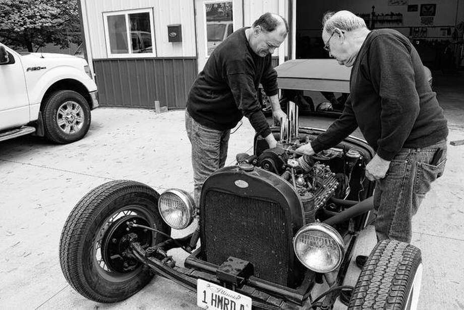 Rick Northrop (left) and his father, Terry Northrop, owner and operator of Terry Northrop Garage at 836 Hardin Ave., work Thursday on a 1951 Mercury engine in a chopped 1931 Ford Model A pickup truck owned by Roger Yeager of Pittsfield.
