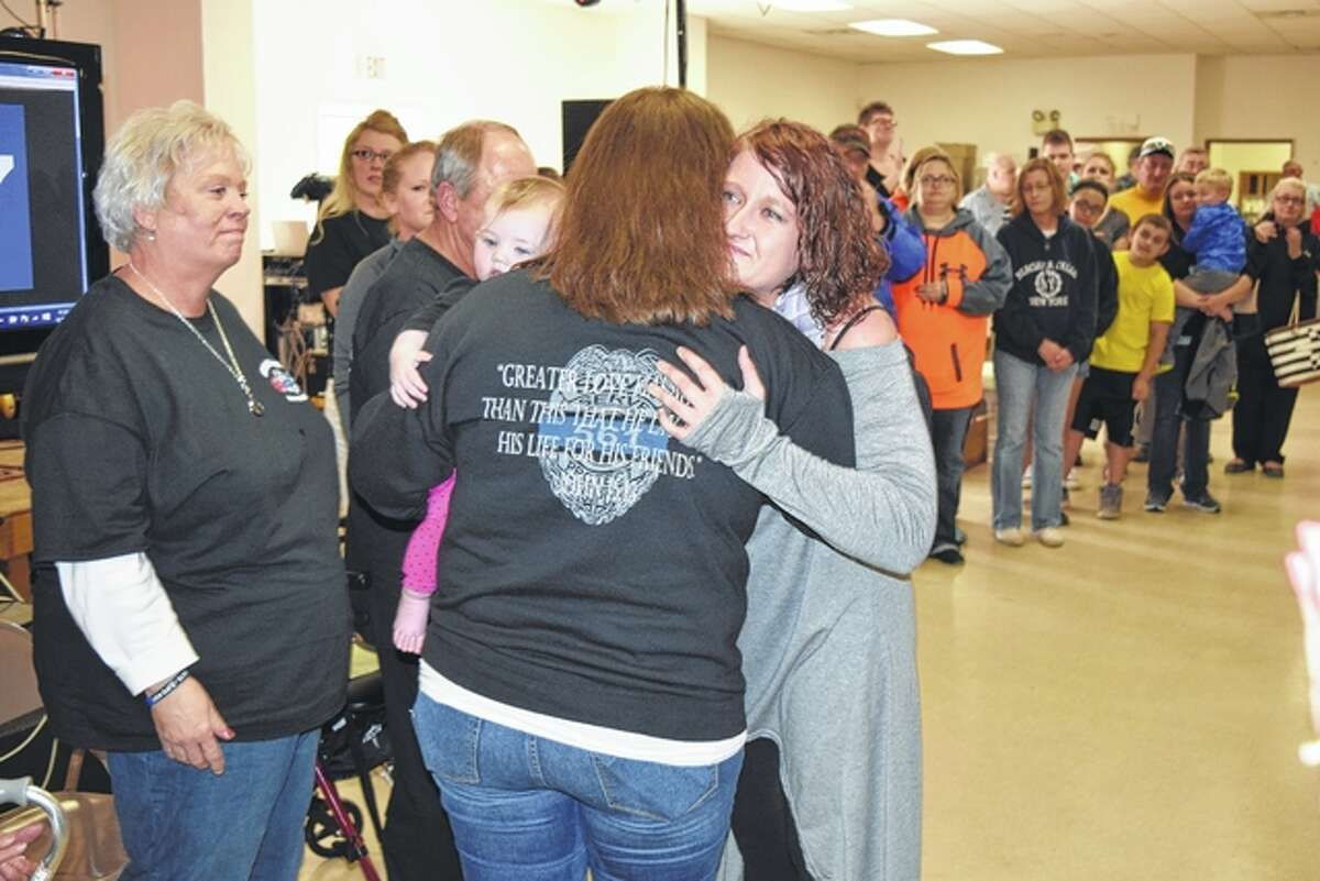 Jacklyn Robson (facing the camera), daughter of the late Bruce Robson, hugs Dani Fitzgerald, widow of the late Scot Fitzgerald, Saturday during a benefit for the Fitzgerald family at the American Legion Post 279 building on West Superior Avenue. Robson presented the proceeds from Saturday's annual Bruce Robson Memorial Open Buddy Bass Tournament to the Fitzgerald family. At left is Becky Fitzgerald, mother of Scot Fitzgerald.