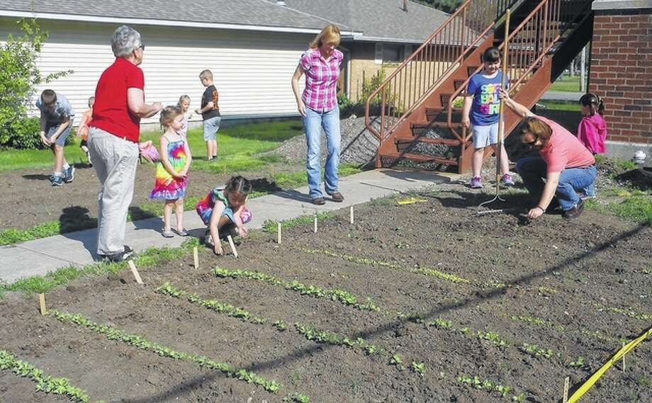 Mary Jo Suter (right), a Sunday school teacher at Waverly First United Methodist Church, helps students from the church work in the garden.