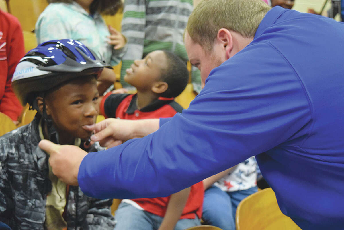 Kyle Nance (right), a junior psychology major at Illinois College, helps Lincoln Elementary School fourth-grader Darius Armstrong adjust his helmet Monday as a part of the Protect the Melon campaign.