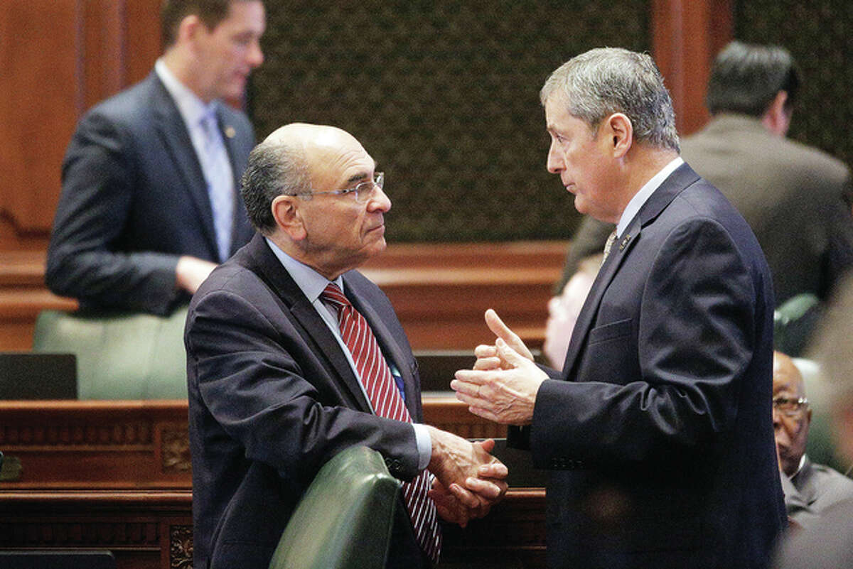 Seth Perlman | AP Rep. Louis Lang (left), D-Skokie, talks with Rep. David Harris, R-Mount Prospect, on the House floor during session Tuesday at the Capitol. House Democrats want the state to tax millionaires at higher rates.