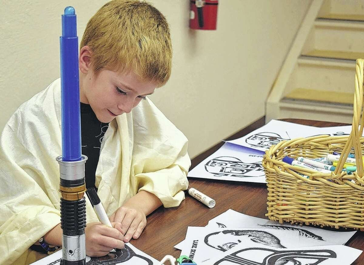 Jack Parlier, 7, son of Brad and Jessica Parlier, of Virginia, dresses as Obi-Wan Kenobi Wednesday during the Virginia Public Library's Star Wars Days.