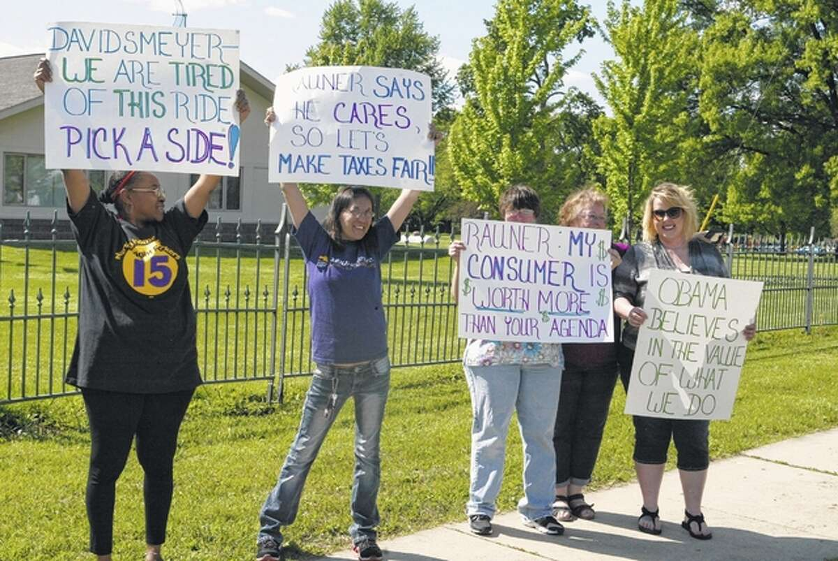 Caregivers hold signs Thursday along Morton Avenue protesting a decision by Gov. Bruce Rauner's administration to stop overtime pay.