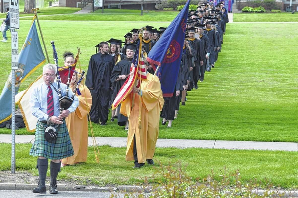 Tom Oglivy leads students and faculty to MacMurray College's commencement ceremony Saturday at Annie Merner Chapel.