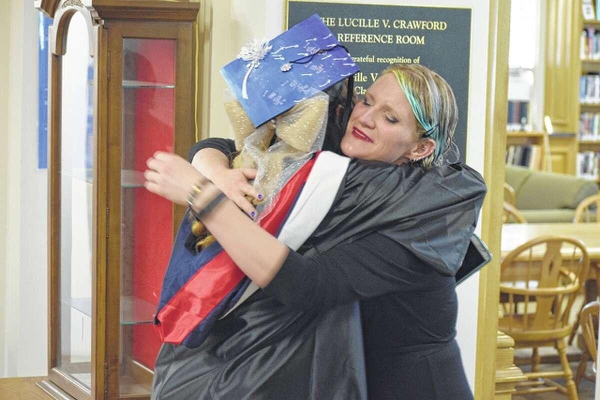 Professor Khara Koffel congratulates student Jennifer Cox, 22, before the commencement ceremony.