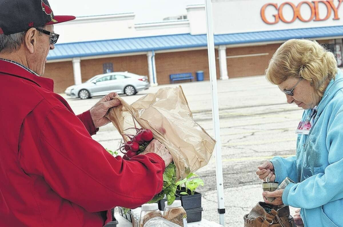 Janet Woods, a teacher at Jacksonville High School, buys radishes Tuesday from Bob Black at the Jacksonville Farmers Market at Lincoln Square Shopping Center. Woods brought the students from her class to see what goods are available at the farmers market.
