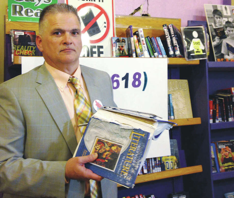 Sara Burnett | AP Harrisburg schools Superintendent Mike Gauch displays a textbooks that is nearly 20 years old and falling apart. Gauch says his district can't afford to replace the books. He's one of several school officials who worry their districts won't have enough money to keep schools open next year if they don't get state money because of the state budget impasse.