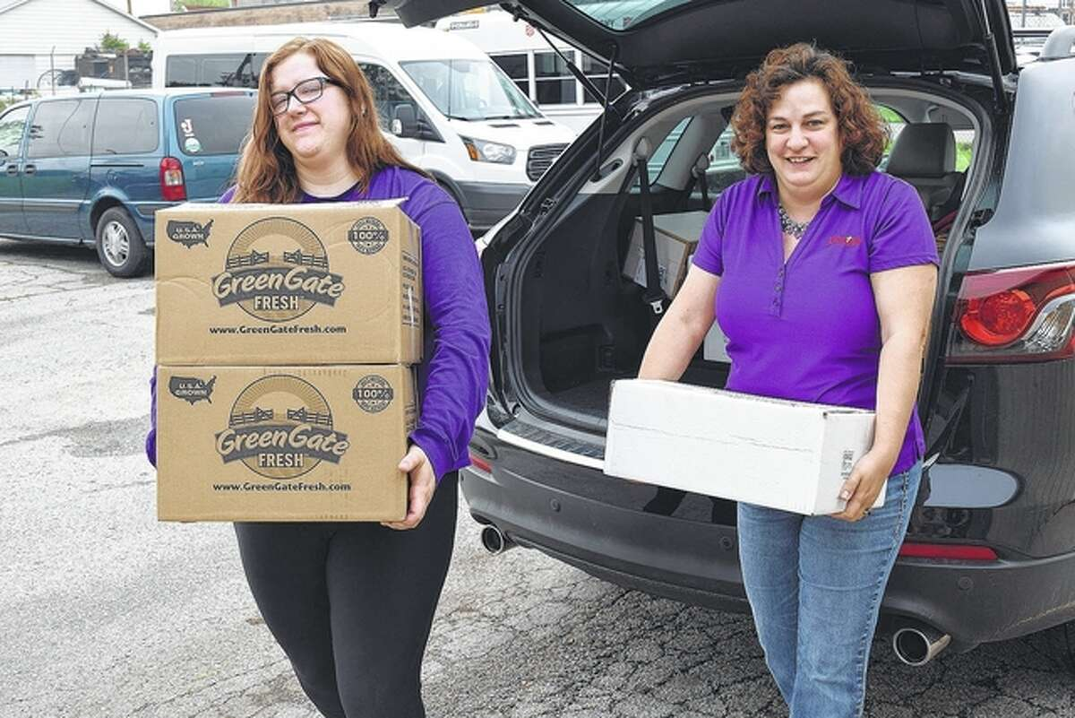 Illinois College sophomore Katy Buhlig of Bluffs (left) and Salvation Army Maj. Katie Pinkston carry food donated Wednesday by IC students into The Salvation Army Citadel on West Douglas Avenue.