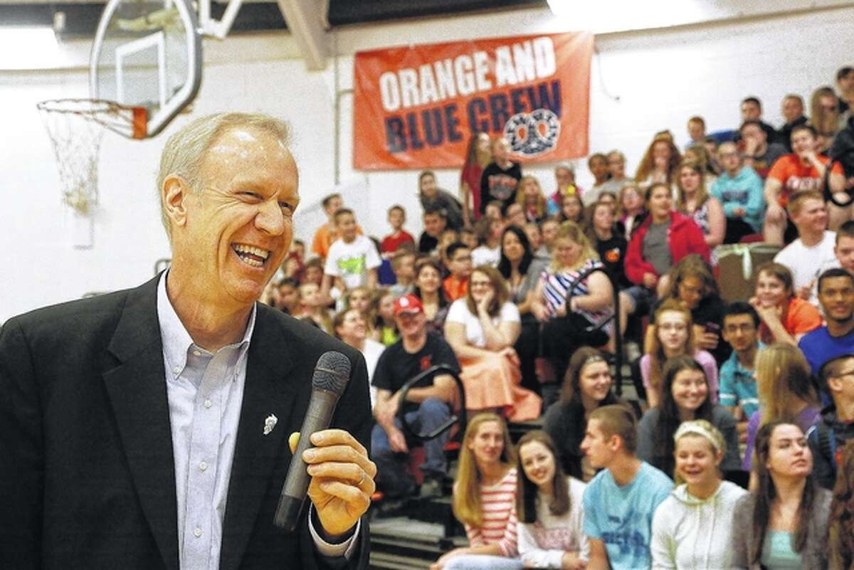 Gov. Bruce Rauner laughs while visiting with students at New Berlin High School on Wednesday. Rauner was touring the school and explaining his education funding reform proposals to students and teachers.