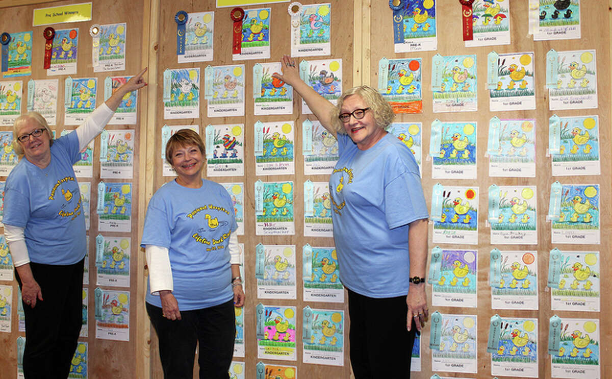 Judges Debbie Richards (from left), Marilyn Kimmons and Barb Hansmeier review a group of entries in the Duck Race for Lifeline coloring contest. Linda Swisher also helped review the entries.