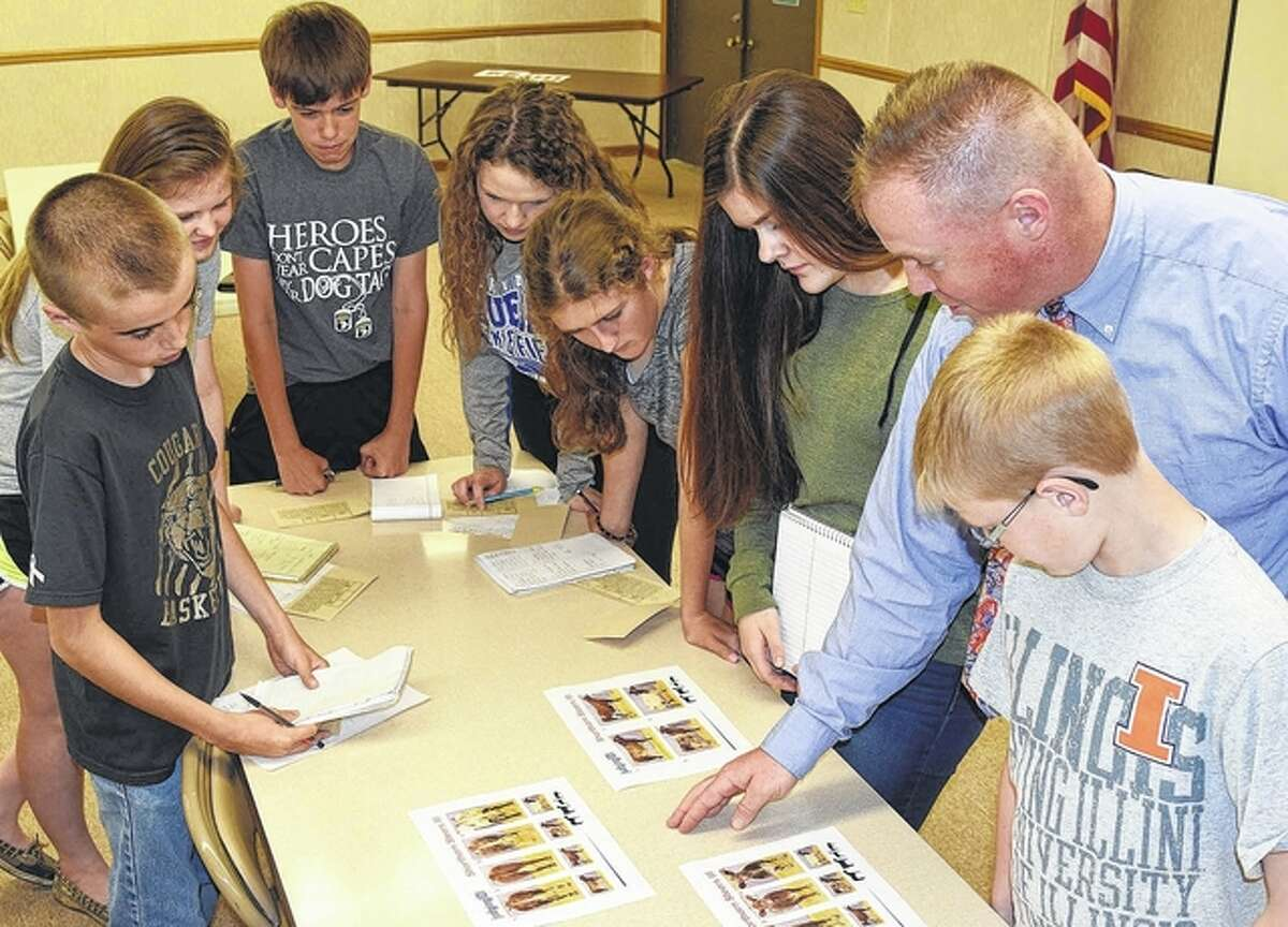 Some of the members of this year's University of Illinois Extension 4-H livestock judging class evaluate images of shorthorn market steers, including Parker Eddinger (clockwise from left) of Winchester, Anne Becker of Jacksonville, Andrew McGath of Jacksonville, Abigail Critchelow of Chandlerville, Kira Sayre of Arenzville, Chasey Tabit of Murrayville, class instructor and coach Aaron Dufelmeier and Alex Dufelmeier of Jacksonville.