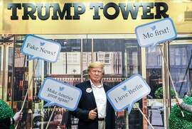TOPSHOT - A waxwork model of US President Donald Trump is framed by famous tweets comments in front of a picture of the New-York Trump Tower at Madame Tussaud's wax museum in Berlin on January 25, 2018.   / AFP PHOTO / dpa / Jens Kalaene / Germany OUTJENS KALAENE/AFP/Getty Images
