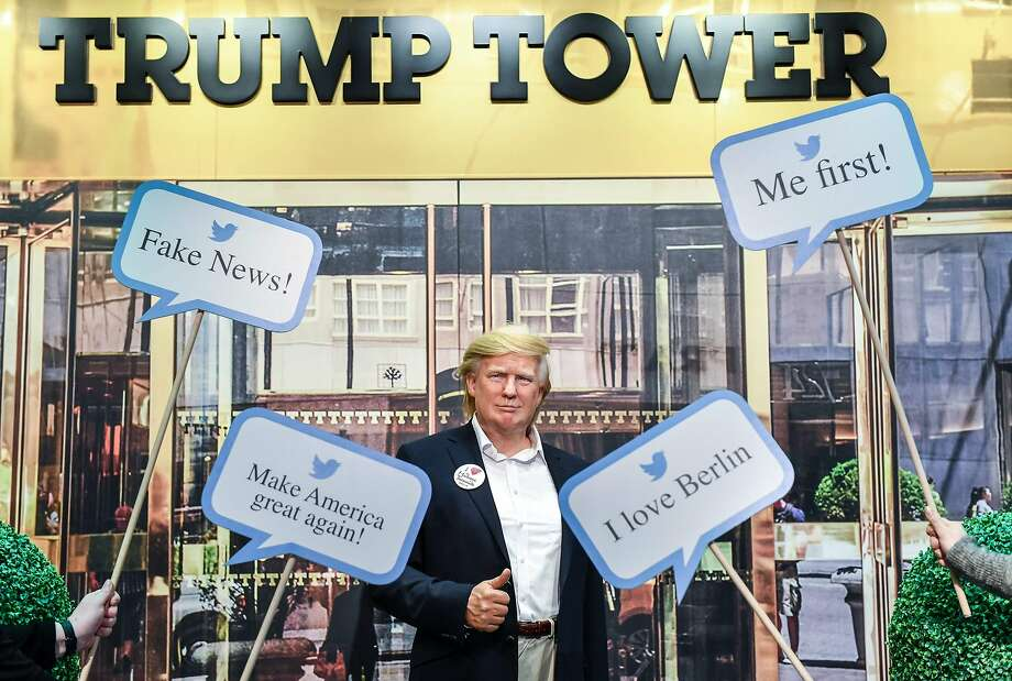 A wax figure of President Trump is framed by tweets by him in front of a photo of Trump Tower at the Madame Tussauds wax museum in Berlin. Trump never rose into the upper echelons of New York society. Photo: JENS KALAENE, AFP/Getty Images
