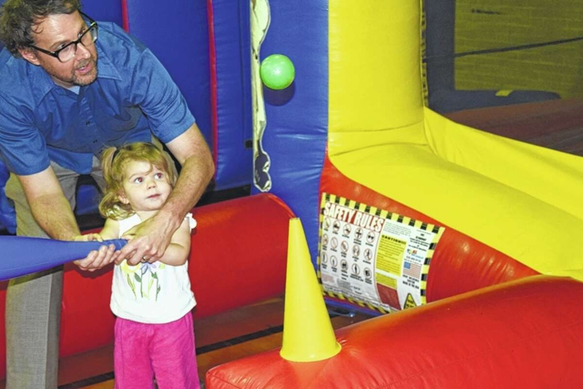Marin Oldenburg, 2, tries to hit a floating ball Friday with the help of her father, Chris Oldenburg, of Jacksonville, at the Illinois College Osage Orange Festival.