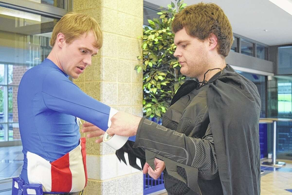 Nate Paulus (right) helps Dan Streib finish his Captain America costume Friday night. Paulus and Steib are members of Superheroes Saving Smiles, a group of people who dress as superheroes and attend different events and visit hospitals to meet and take pictures with children.