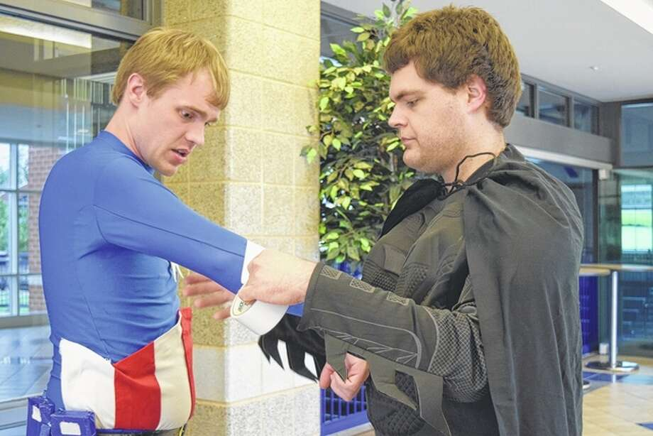 Nate Paulus (right) helps Dan Streib finish his Captain America costume Friday night. Paulus and Steib are members of Superheroes Saving Smiles, a group of people who dress as superheroes and attend different events and visit hospitals to meet and take pictures with children. Photo: Samantha McDaniel-Ogletree | Journal-Courier