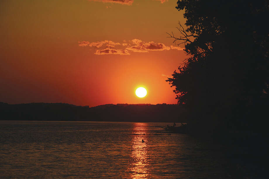 A glowing sun sets over the Mississippi River.