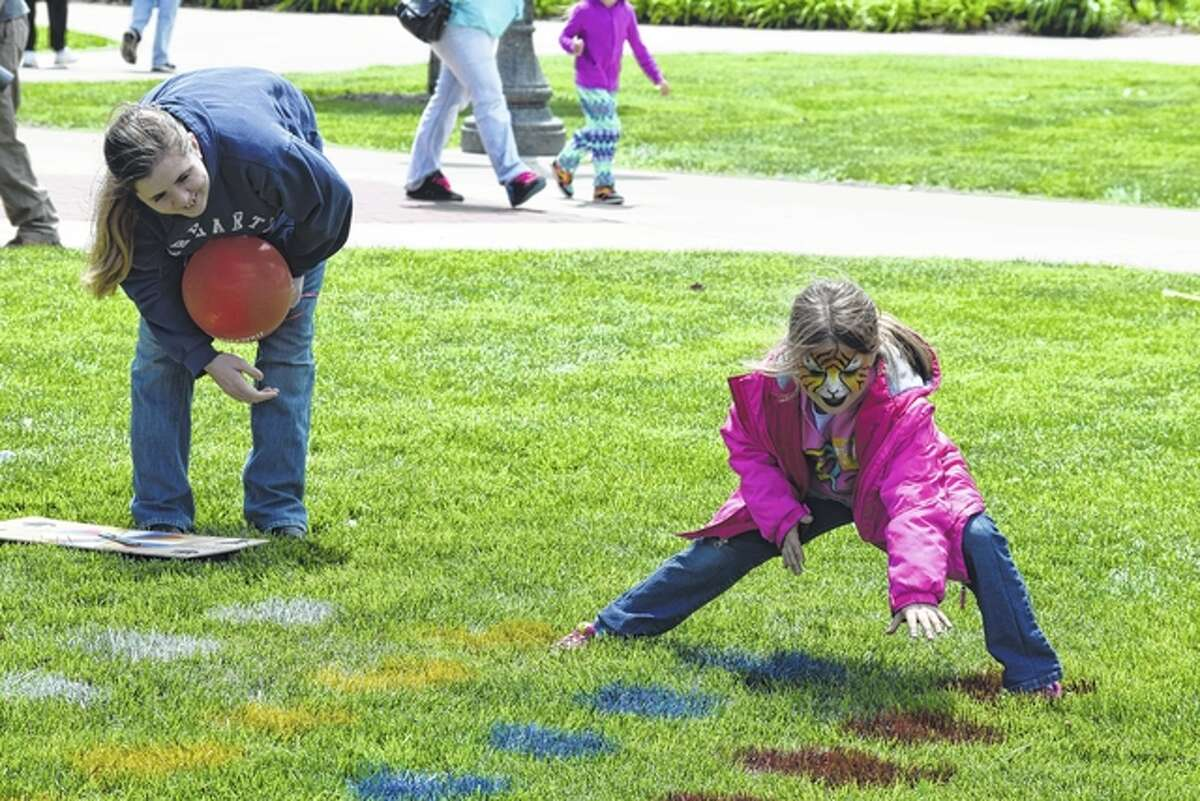 A young girl puts right-foot red at a game of Twister at the Downtown Celebration.