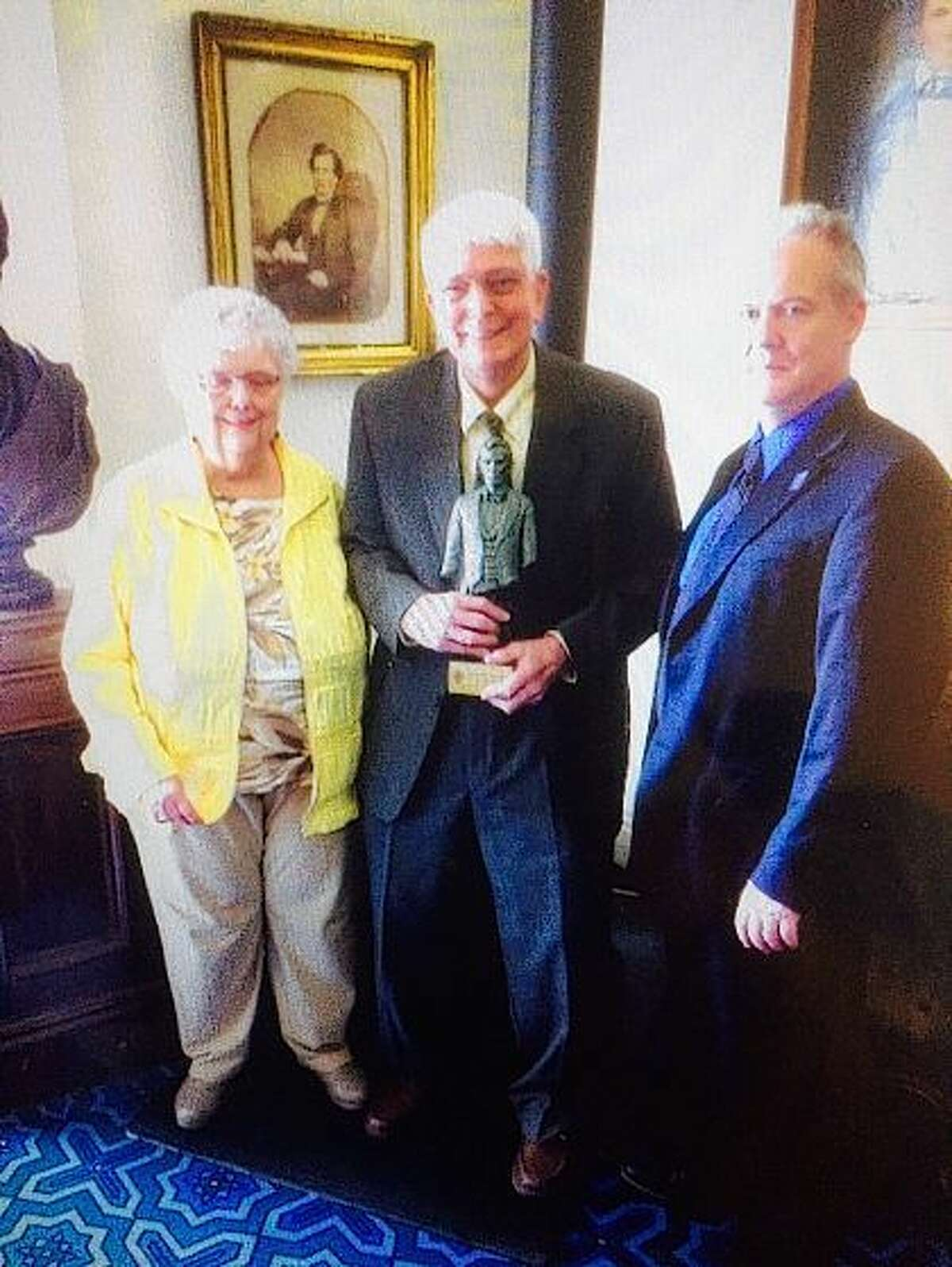 Patricia and Rand Burnette of Jacksonville accept the Lifetime Achievement award from the Illinois State Historical Society at the society's 117th annual meeting. Presenting the award is Chris McDonald, co-chairman of the ISHS Annual Awards Committee.