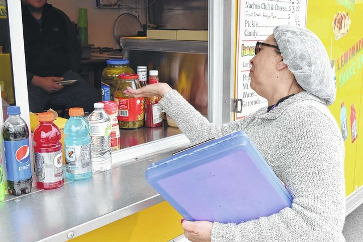 Linda Day, food program manager for the Morgan County Health Department, inspects food trucks Saturday during the Downtown Celebration.
