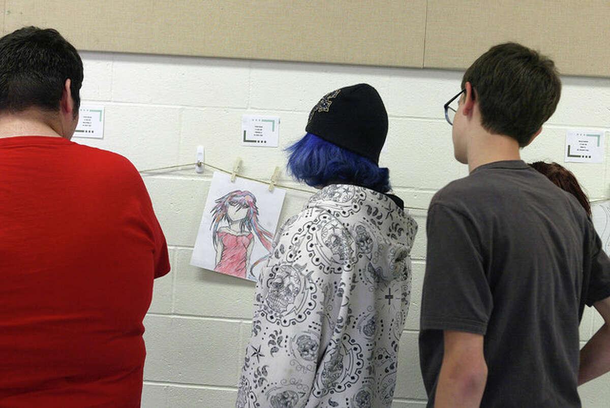 Students from Garrison Alternative School look at artwork Monday in the school caferteria.