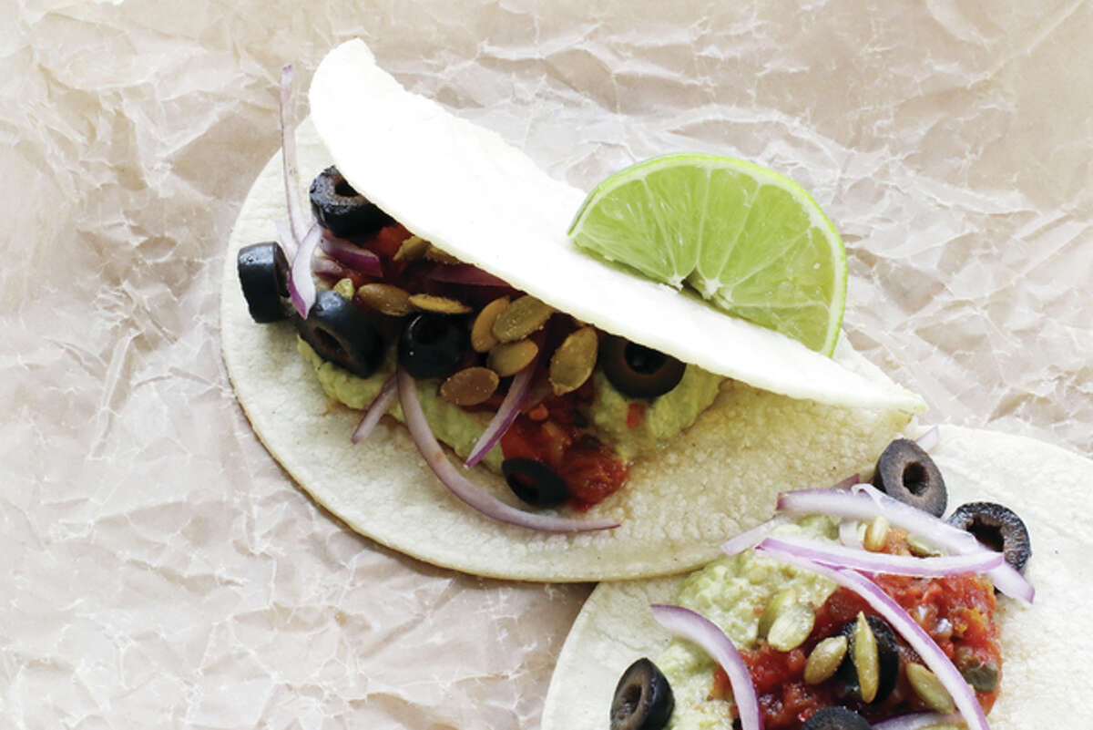 Refried edamame in a flour tortilla is garnished with lime, toasted pumpkin seeds, olives and onions.