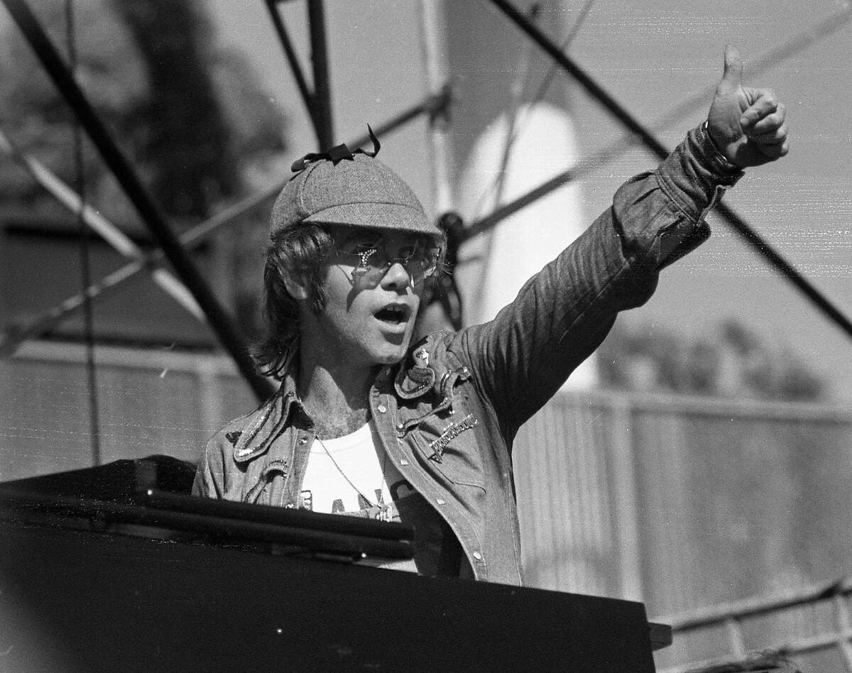 Unscheduled to perform Elton John surprises that audiences by playing piano with both the Doobie Brothers and thee Eagles at the Day on the Green held at the Oakland Coliseum, June 30, 1975