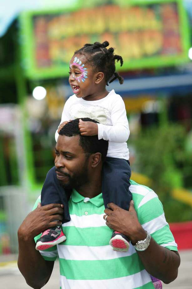 Krista Monet Hooper, 2, laughs as she rides on the shoulders of her father, Shaun Hooper, on the opening day of the Houston Livestock Show and Rodeo Tuesday, March 7, 2017 in Houston. ( Michael Ciaglo / Houston Chronicle ) Photo: Michael Ciaglo, Staff / Michael Ciaglo