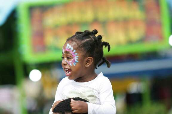 Krista Monet Hooper, 2, laughs as she rides on the shoulders of her father, Shaun Hooper, on the opening day of the Houston Livestock Show and Rodeo Tuesday, March 7, 2017 in Houston. ( Michael Ciaglo / Houston Chronicle )