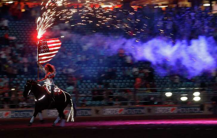 A woman carrying an American Flag, rides a horse bareback during the National Anthem before the start of the Super Series II, Round 1, at the Houston Livestock Show and Rodeo, at NRG Park, Friday, March 10, 2017, in Houston.  ( Karen Warren / Houston Chronicle )