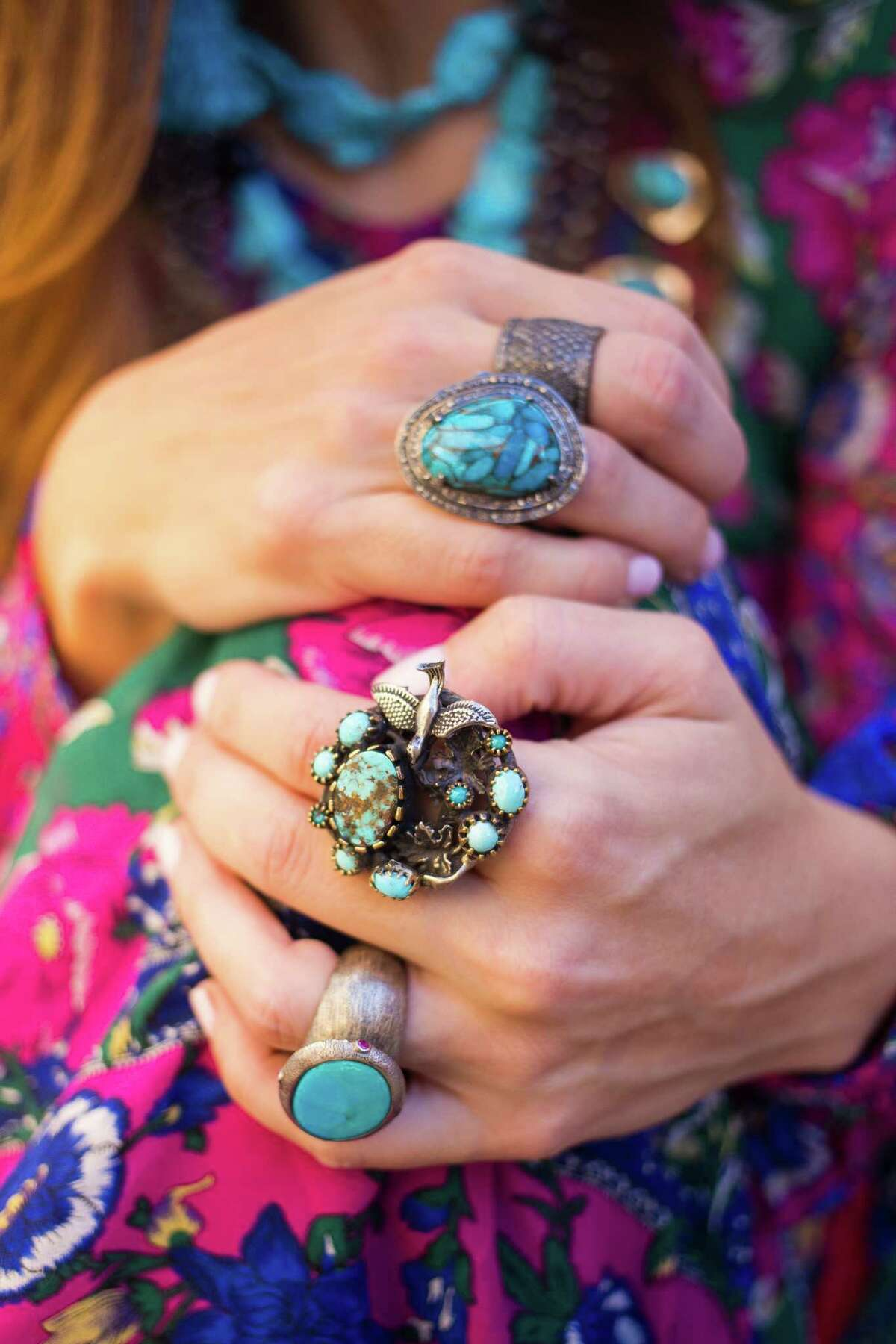 RODEO FASHION: Dress from Anthropologie - $228. Squash blossom necklace - $1,800, Seeping Beauty turquoise necklaces (she�'s wearing two of the same necklace) - $300 each, Turquoise tassel earrings - $35, RINGS (from top to bottom in photo) Champagne diamond cigar band - $600, Turquoise ring with diamond surround - $375, Turquoise ring with sterling silver bird - $342, and Turquoise and sterling silver ring - $225. All from J. Landa in Rice Village