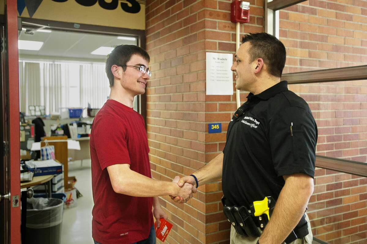 Eddie Hinson, Midland High's new School Resource Officer, shakes the hand of Midland senior Joshua McClelland after Hinson gave McClelland a Nike gift card he won from Project 111, which celebrates safe drivers, on Tuesday, Feb. 6, 2018 at Midland High. (Katy Kildee/kkildee@mdn.net)